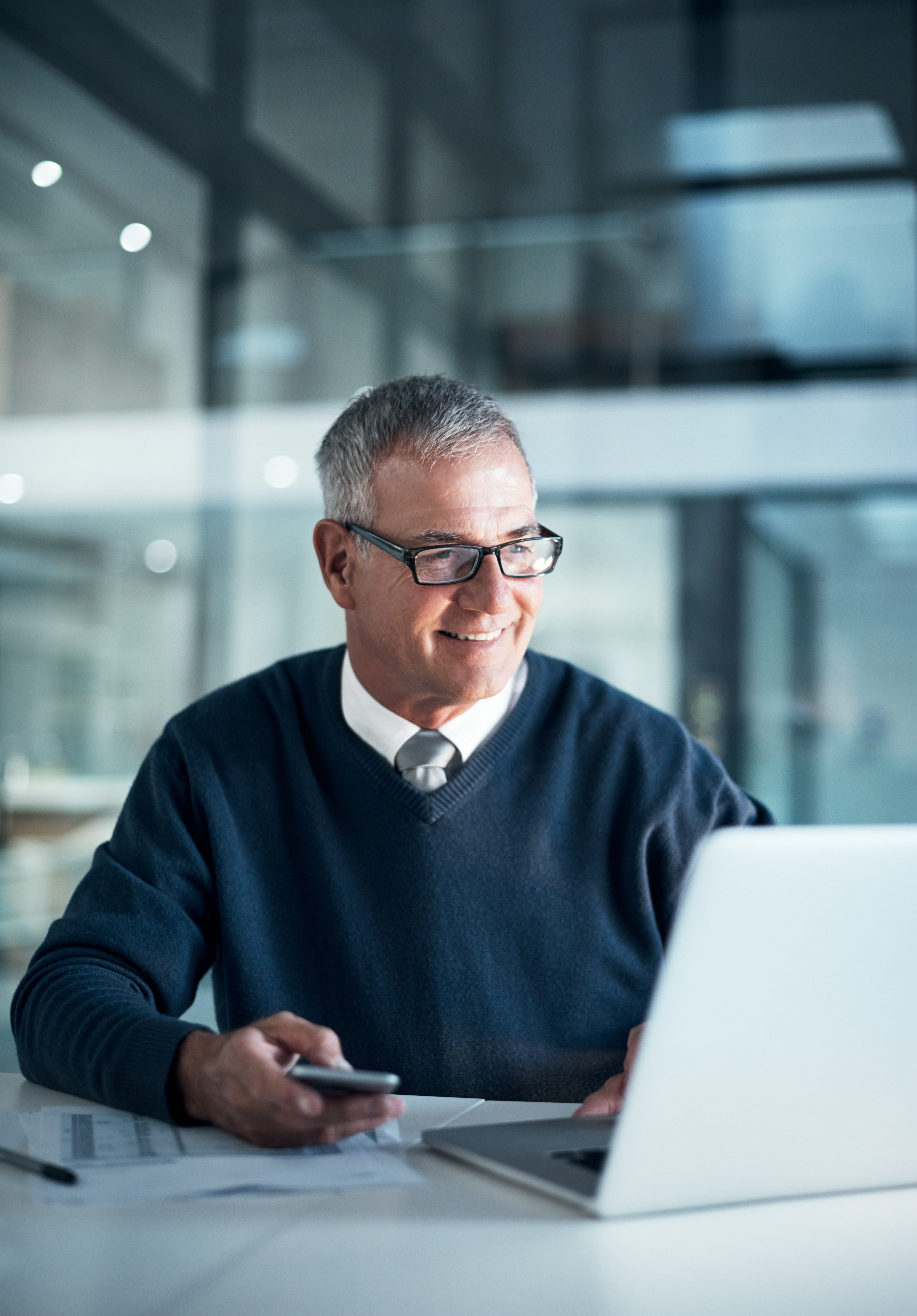 Employee using mobile device and laptop