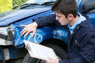 Carubba Collision man evaluating damage to a vehicle
