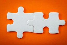 Interlinking puzzle pieces on orange background