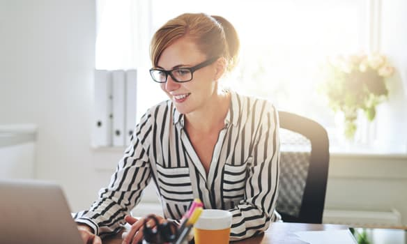 Woman working on a laptop   paperless invoice processing solutions