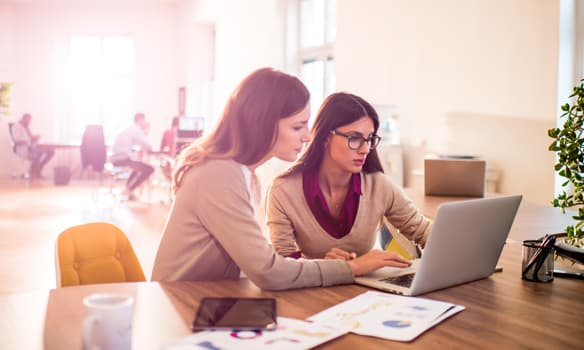 Two women working on a laptop   paperless sales and marketing solutions