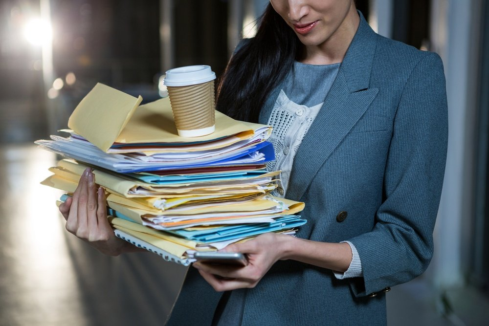 Businesswoman carrying stack of file folders while using mobile phone in the office.jpeg
